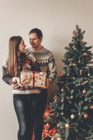 joyeux Noël et bonne année concept. couple élégant hipster, échanger des cadeaux dans la salle festive sous l'arbre de Noël avec des lumières, un espace pour le texte. joyeuses fêtes. moments atmosphériques familiaux