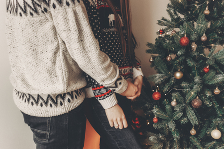 couple heureux dans les chandails élégants décorant le sapin de Noël. joyeux Noël et bonne année concept. espace pour le texte. femme et homme étreindre. moments agréables en famille Banque d'images