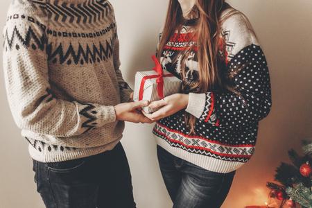 joyeux Noël et bonne année concept. couple élégant hipster en chandails tenant un cadeau avec un arc rouge dans la salle de fête à l'arbre de Noël avec des lumières. joyeuses fêtes. moments en famille