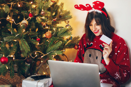 stylish woman in reindeer hat holding credit card and laptop buying gifts, under christmas tree lights. shopping online, sale. space for text. seasonal greetings, happy holidays. 스톡 콘텐츠