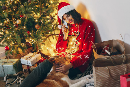 happy woman in santa talking on phone and sitting with dog under christmas tree lights. space for text. merry christmas and happy new year concept. seasonal greetings, happy holidays