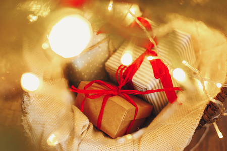 stylish craft gifts in basket under christmas tree with garland lights and golden ornaments. space for text. seasonal greetings, happy holidays. merry christmas and happy new year concept.
