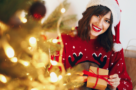 woman in santa hat holding stylish gift under christmas tree with garland lights and golden ornaments. space for text. seasonal greetings, happy holidays. merry christmas