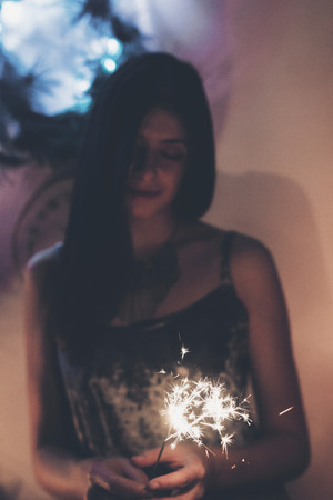 happy stylish woman holding a burning sparkler firework bengal light. space for text.  sparks closeup in female hand in dark. happy new year and merry christmas concept. happy holidays