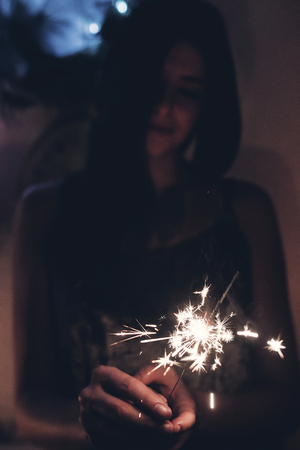 happy new year and merry christmas concept. happy stylish woman holding burning sparkler firework bengal light. space for text.  shining fire flame fireworks. happy holidays. toned