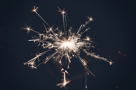 burning sparkler firework bengal light. space for text. burning sparks closeup in  hand in dark. happy new year and merry christmas concept. happy holidays. pyrotechnics, shining fire flame