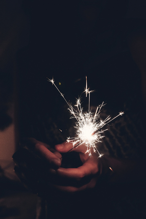 hand holding a burning sparkler firework bengal light. space for text. burning sparks closeup in female hand in dark. happy new year and merry christmas concept. happy holidays, toned