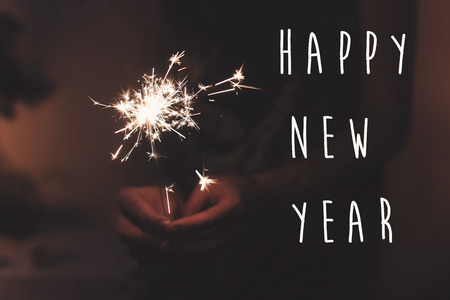 happy new year text sign, hand holding a burning sparkler firework bengal light. space for text. burning sparks closeup in female hand in dark. happy new year and merry christmas concept. happy holidays