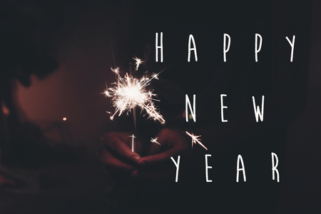 happy new year text sign, happy new year and merry christmas concept. hand holding burning sparkler firework bengal light. space for text. pyrotechnics concept, shining fire flame fireworks. happy holidays. toned