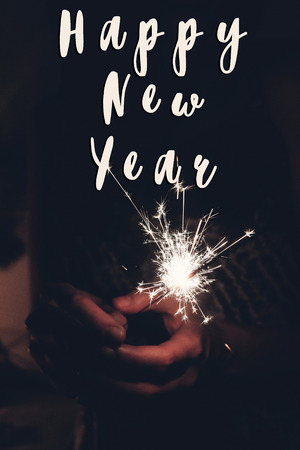 happy new year text sign, hand holding a burning sparkler firework bengal light. space for text. burning sparks closeup in female hand in dark. happy new year and merry christmas concept. happy holidays, toned