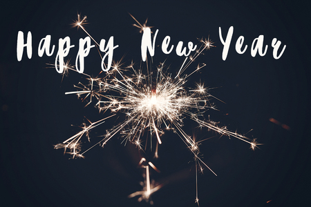 happy new year text sign, burning sparkler firework bengal light. space for text. burning sparks closeup in  hand in dark. happy new year and merry christmas concept. happy holidays. pyrotechnics, shining fire flame