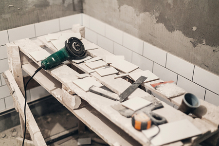 grinder and stylish white tiles for cutting. renovation concept. ceramic tiles  and grey cement walls in bathroom, renovating and working in toilet, space for text Zdjęcie Seryjne