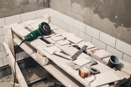 molen en stijlvolle witte tegels om te snijden. renovatie concept. keramische tegels en grijze betonnen muren in de badkamer, renoveren en werken in toilet, ruimte voor tekst Stockfoto