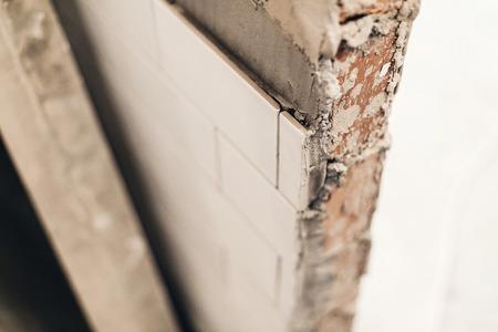 moderne witte tegels op de muur, renovatie concept. keramische tegels en grijze bakstenen muren in badkamer, renoveren en werken in toilet, ruimte voor tekst. repareren Stockfoto
