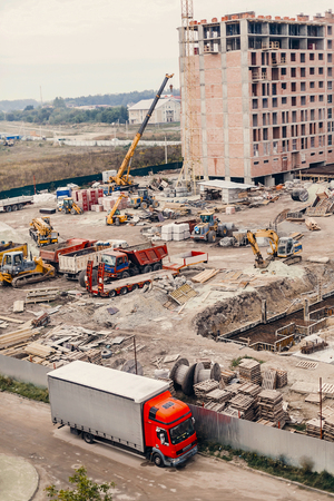 Construction Site, construction machinery, bulldozer, excavation, factory,  cranes and sand. house building area in the city. brick walls and pit holes and foundations