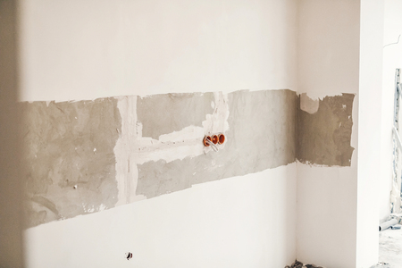 renovation concept. electric wires and cables in holes in grey cement wall. repairing and working in home, space for text. wall background
