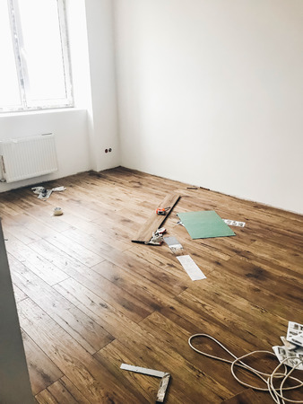 room floor renovation concept. stylish wooden laminate instalation, modern white walls. repairing and working in home, space for text. hardwood plank parquet. renovating Banco de Imagens