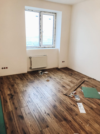 room floor renovation concept. stylish wooden laminate instalation, modern white walls. repairing and working in home, space for text. hardwood plank parquet. renovating Stock Photo