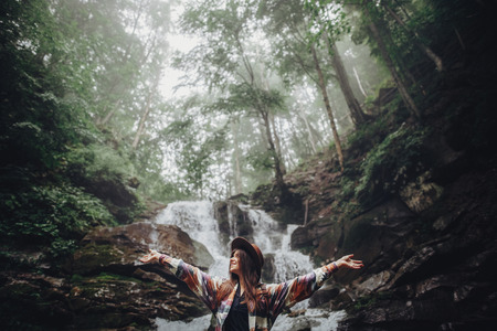 happy stylish traveler girl in hat relaxing at waterfall, atmospheric moment of success. hipster woman with backpack travelling, hands up. space for text. wanderlust and travel concept