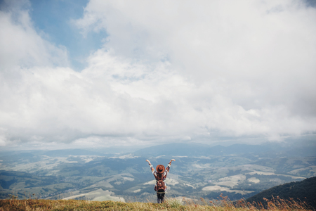 wanderlust and travel concept. girl traveler in hat with backpack raising hands up in mountains. stylish hipster woman on top of mountain in clouds. space for text. atmospheric moment