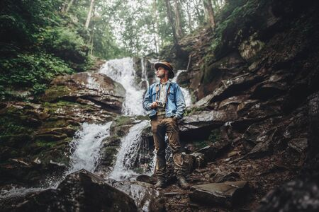 wanderlust and travel concept. stylish traveler man in hat posing at waterfall, holding photo camera, exploring woods. hipster man with backpack traveling in forest. space for text Standard-Bild
