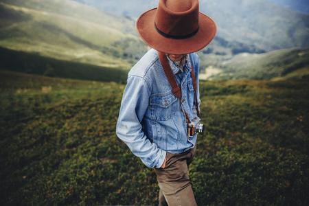 방황 및 여행 개념. 산 꼭대기에 서있는 사진 카메라로 모자에서 남자 여행자. 세련 된 성공적인 hipster 야외에서 탐험입니다. 텍스트위한 공간입니다.