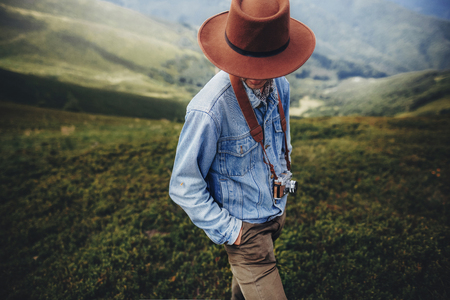 wanderlust and travel concept. man traveler in hat with photo camera standing on top of mountain. stylish successful hipster exploring outdoors. space for text. atmospheric moment Stok Fotoğraf