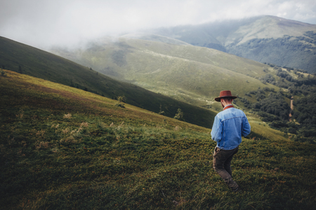 wanderlust and travel concept. man traveler in hat with photo camera walking on top of misty mountain. stylish hipster exploring outdoors. space for text. atmospheric moment
