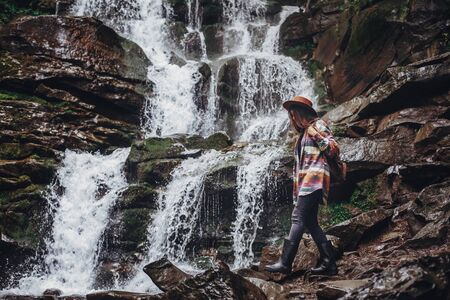 wanderlust and travel concept. stylish traveler girl holding hat looking at waterfall, exploring woods. hipster woman with backpack travelling at river in forest. space for text Standard-Bild