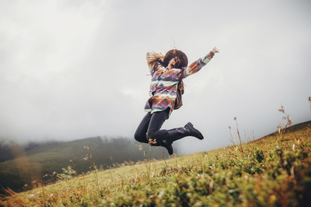 stylish traveler girl in hat with backpack jumping in mountains. happy hipster woman having fun on top of mountain. space for text. wanderlust and travel concept. atmospheric moment