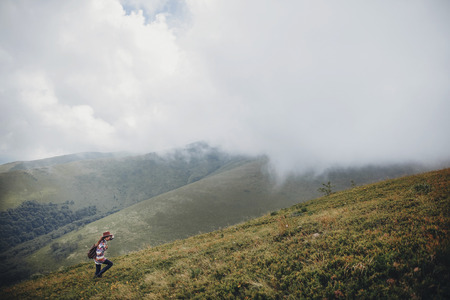 wanderlust and travel concept. girl traveler in hat with backpack walking in clouds in mountains. stylish hipster woman exploring on top of mountain. space for text. atmospheric moment