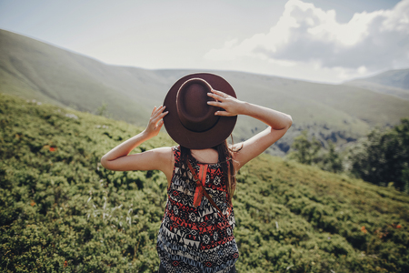 wanderlust and travel concept. stylish traveler woman in hat looking at mountains. hipster girl traveling on top of mountain, raising hands. space for text. atmospheric moment