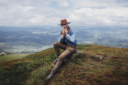 wanderlust and travel concept. man traveler in hat with photo camera sitting on top of mountains. stylish hipster taking photo. space for text. atmospheric moment