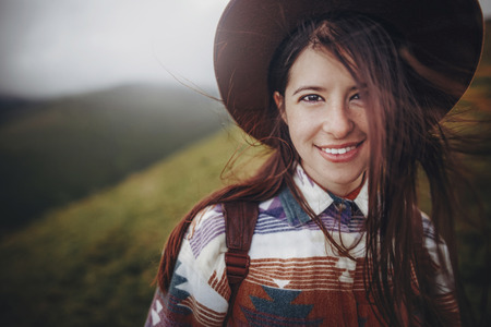 stylish traveler girl portrait in hat with backpack in mountains. hipster woman with windy hair looking on top of mountain. space for text. wanderlust and travel concept. atmospheric moment Standard-Bild