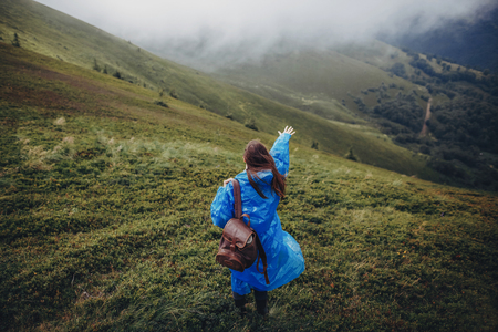 wanderlust and travel concept. girl traveler in raincoat with backpack walking in clouds in mountains. stylish hipster woman exploring. space for text. atmospheric moment
