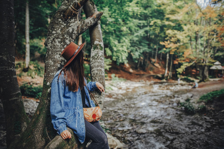 stylish traveler girl in hat exploring woods. hipster woman travelling in the forest, sitting on tree at river. space for text. wanderlust and travel concept