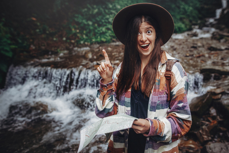 happy stylish traveler girl in hat holding map and showing finger up, moment of success and idea. hipster woman with backpack travelling. space for text. wanderlust and travel concept