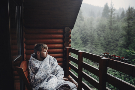 stylish man traveler in blanket relaxing on porch of wooden cabin in rainy day on background of woods in mountains. stylish hipster resting. space for text. atmospheric moment Standard-Bild