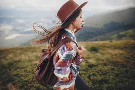 stylish traveler girl in hat with backpack walking in mountains. hipster woman exploring on top of mountain. space for text. wanderlust and travel concept. atmospheric moment Archivio Fotografico