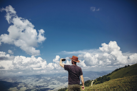 stylish traveler man in hat holding phone in mountains. hipster  on top of mountain in the sky and clouds, taking photo and video of landscape. space for text. wanderlust and travel concept