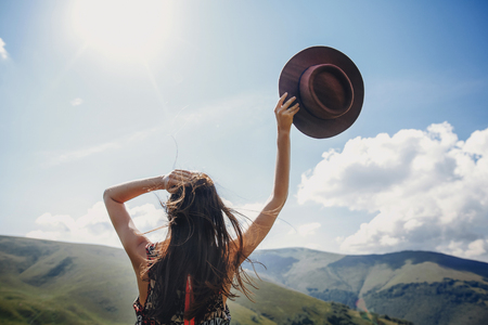 stylish traveler woman looking at mountains. hipster girl on top of mountain, raising hands and holding hat in sky. space for text. atmospheric epic moment. wanderlust and travel concept