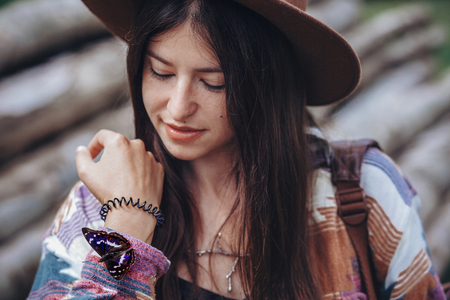 happy stylish traveler girl in hat holding beautiful colorful butterfly on hand. hipster woman travelling and exploring. space for text. environmental and discovery concept.  Apatura iris Standard-Bild