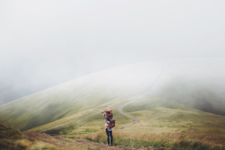 stylish traveler girl in hat with backpack walking in mountains. hipster woman exploring on top of mountain. space for text. wanderlust and travel concept. atmospheric moment Stockfoto