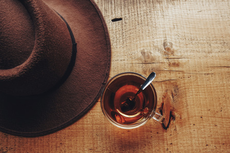 wanderlust and travel concept. hat and hot tea on wooden table, top view. travel flat lay with space for text. hot drink in cabin on top fo mountains
