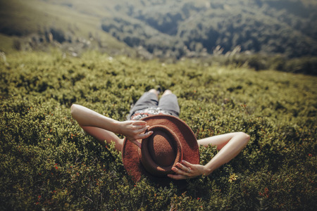 stylish traveler woman in hat lying on grass and relaxing in mountains. hipster girl on top of mountain, resting, hat on her face. space for text. atmospheric moment. wanderlust and travel concept. Archivio Fotografico