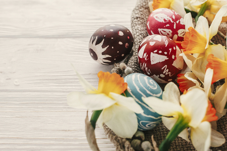modern easter image. stylish colorful easter eggs with spring flowers daffodils on rustic white wooden background top view. space for text. stylish painted eggs. greeting card Standard-Bild