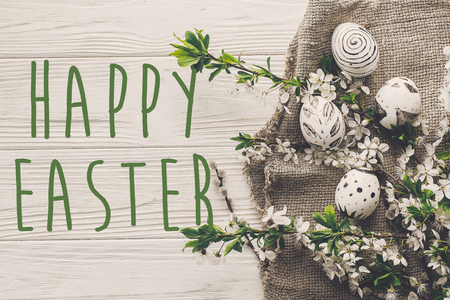 happy easter text flat lay with flowers and stylish eggs on rustic wooden background top view. modern green easter greeting card. space for text