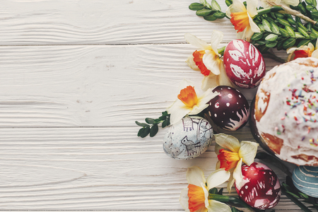 happy easter flat lay, stylish easter bread and painted eggs on rustic wooden background top view with candle yellow flowers and greenery.  greeting card. space for text Stockfoto
