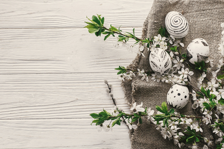 modern easter flat lay. stylish easter eggs on rustic white wooden background with fresh spring flowers top view. space for text. stylish painted eggs. seasonal greeting card Standard-Bild