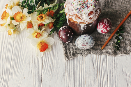 stylish easter bread and painted eggs on rustic wooden background top view with candle yellow flowers and greenery. happy easter flat lay, greeting card. space for text